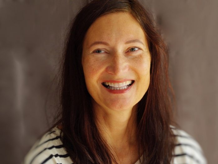 lachende Frau mit langen dunklen Haaren vor dunklem Hintergrund