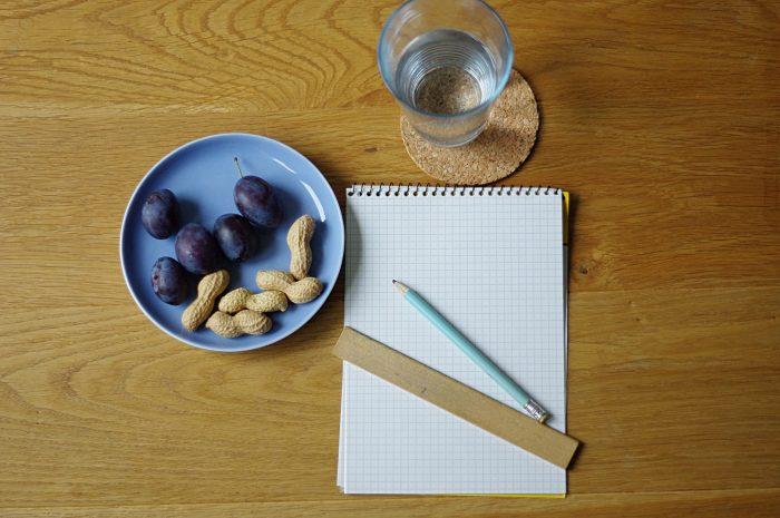 unbeschriebener Notizblock, Lineal, Bleistift, Wasserglas, Teller mit Nüssen und Pflaumen auf Schreibtisch