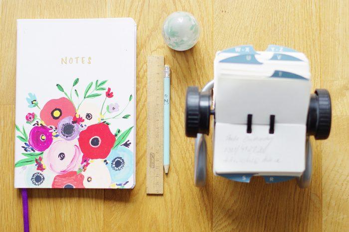 Notizbuch, Lineal, Bleistift und Rolodex auf Schreibtisch