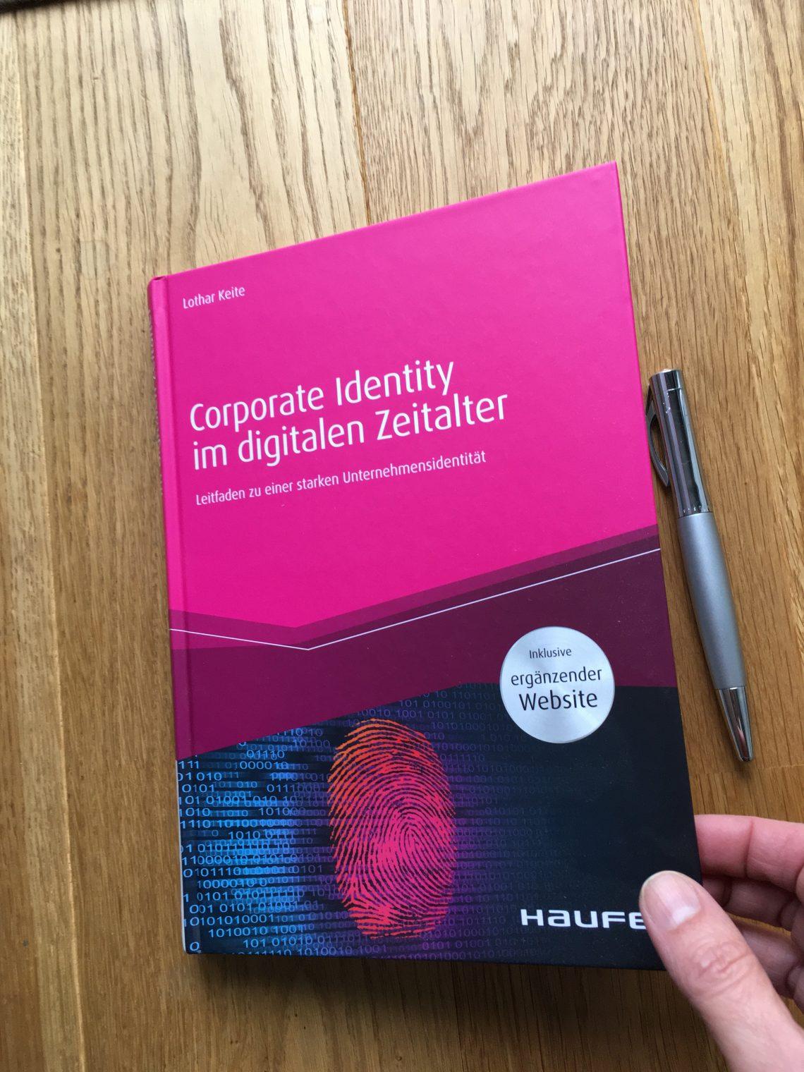 """Hand hält Buch """"CI im digitalen Zeitalter"""", Füller liegt daneben"""